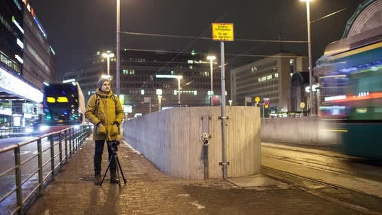 Thumbnail for Timelapse of Man Shooting Video in Night Helsinki with Transport Traffic