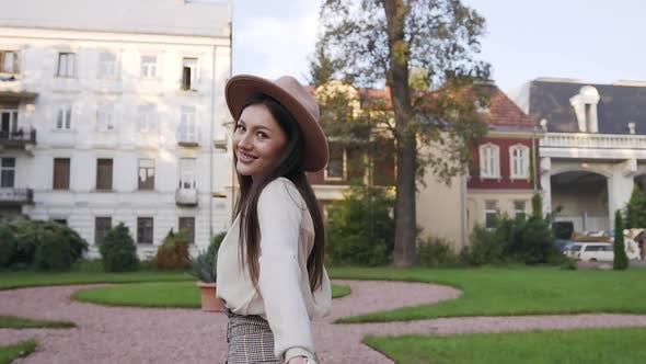 Thumbnail for Smiling Carefree Lady with Long Brown Hair and Stylish Hat Turning Around and Looking at Camera