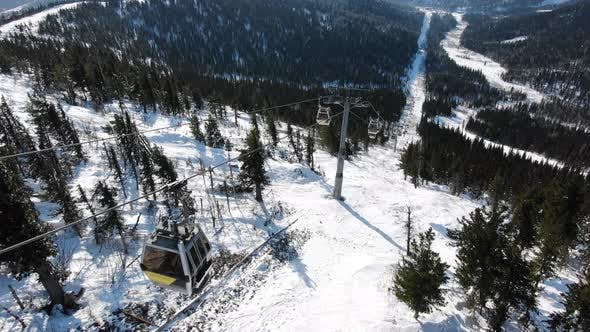 modern ski lift cabins move over extreme tracks on hill
