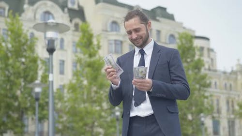 Confident Successful Rich Businessman Counting Dollars and Smiling. Portait of Happy Caucasian Young