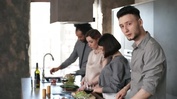 Cover Image for Young Man Cooking with Friends and Smiling for Camera