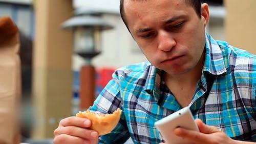 Man Eating A Hamburger And Talking On The Phone