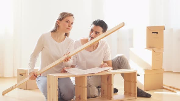 Couple Installing Furniture in New House with Instruction