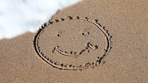 Smiley Face Sign On The Beach Sand