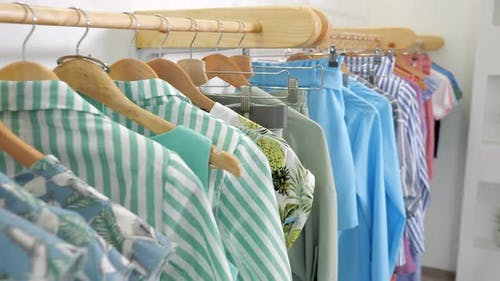Wooden Hangers with Fashionable Colorful Clothes on Rack