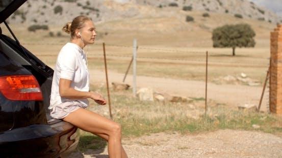 Thumbnail for Girl In White Sweatshirt Sitting On Car Trunk