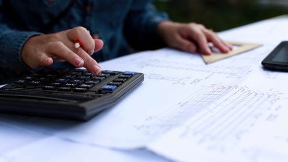 Architect make calculations on a calculator