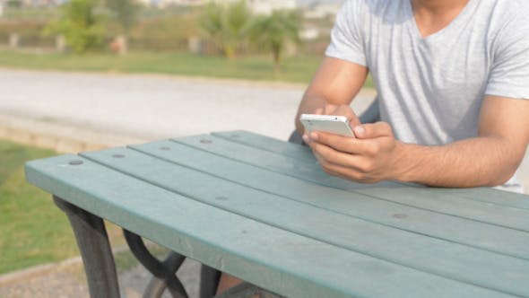 Thumbnail for Young Man Using Phone, while Sitting in Park