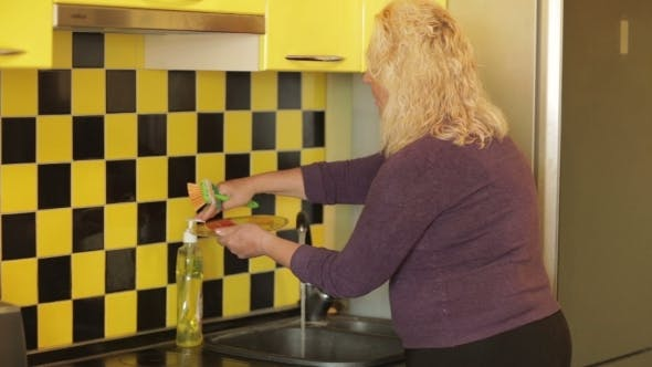 Thumbnail for Middle-aged Woman Washing a Plate In The Kitchen