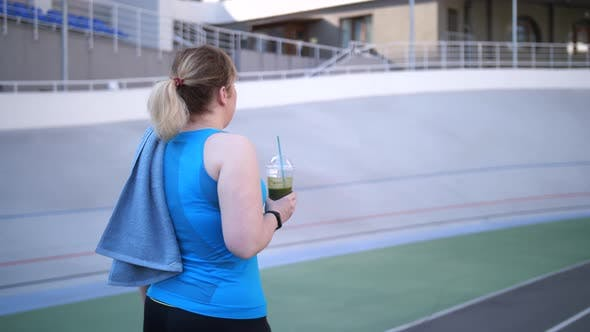 Thumbnail for Plus Size Woman Jogger Walking with Smoothie Drink