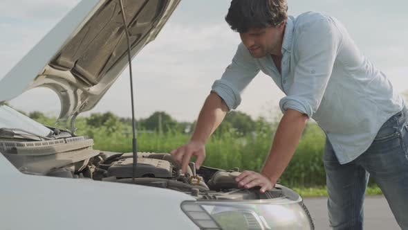 Thumbnail for Man Standing Next To a Broke Down Car, Looking Down at Engine in Frustration