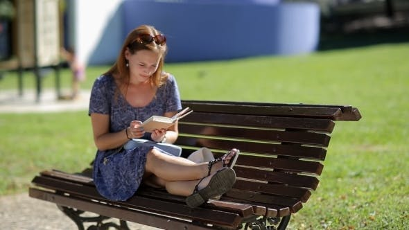 Thumbnail for Young Woman Relaxing, Reading a Book And Sitting