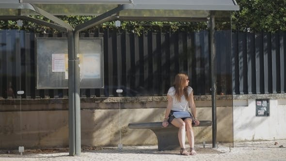 Thumbnail for Lonely Young Girl Waiting At Bus Stop In Skirt