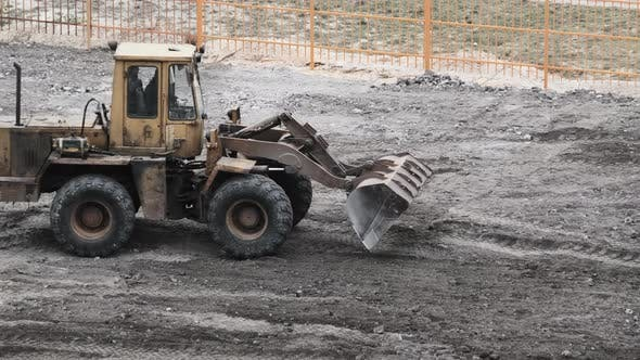 Cover Image for An Old Bulldozer on Rubber Wheels Works on Construction Site.