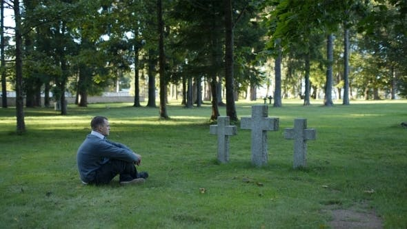 Thumbnail for Man Sitting Mourning In Front Of Three Crosses