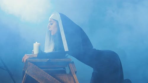 Attractive Sexy Nun Blows Out a Candle in a Dark Smoky Studio