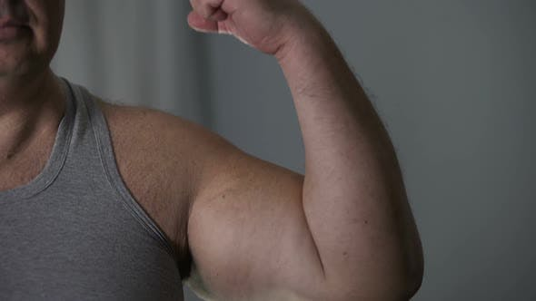Thumbnail for Unhealthy Overweight Male Showing His Weak Biceps Before Camera