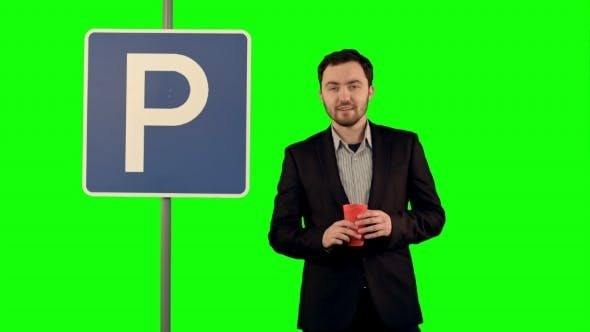 Thumbnail for Man With Cup Of Tea Near Parking Sign On a Green