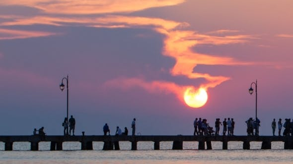 Thumbnail for Timelapse Of People Walking On Pier At Sunset