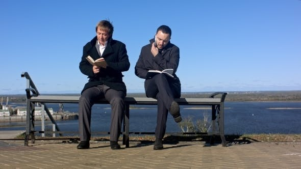 Cover Image for Two Men Sitting Outdoors On a Bench With a Book