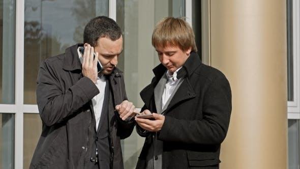 Thumbnail for Two Businessmen Talking On Mobile Phone And