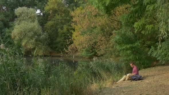 Thumbnail for Man Sitting at The Lake Looking in Front of Him