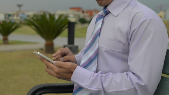 Businessman Using Smartphone, Sitting on Bench