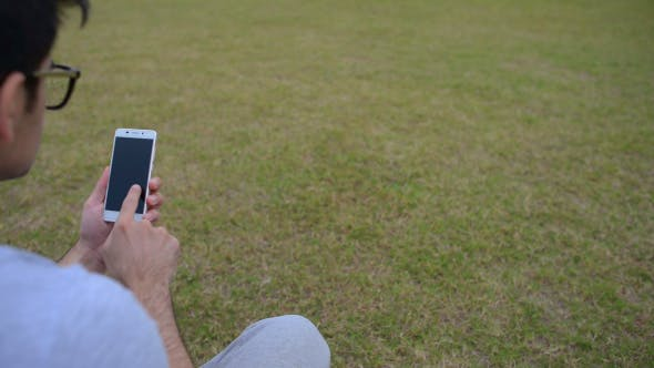 Thumbnail for Smartphone, Man Using while Sitting on Grass