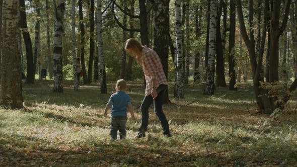 Mother With Son Walking Outdoor In Autumn.