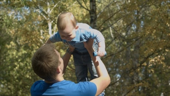 Thumbnail for Dad Tosses Son Into The Air In An Autumn Park