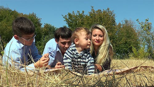 Family Lying in the Meadow Facing the Camera