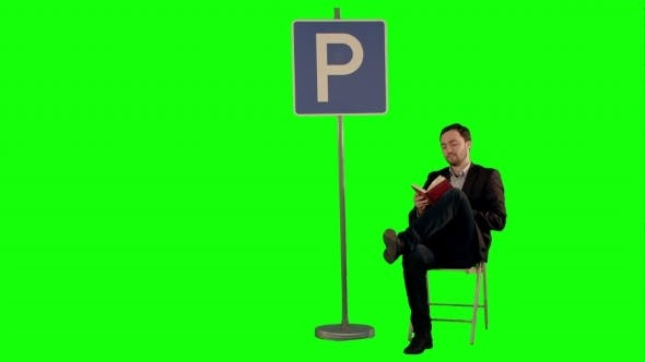 Thumbnail for Businessman Reading a Book Near Parking Sign On a