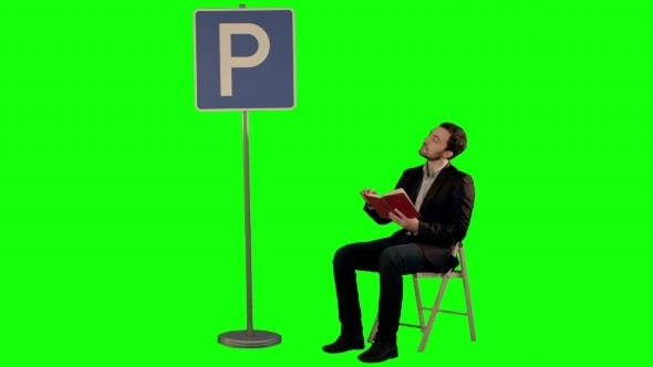 Thumbnail for Young Man Reading a Book Near Parking Sign On a