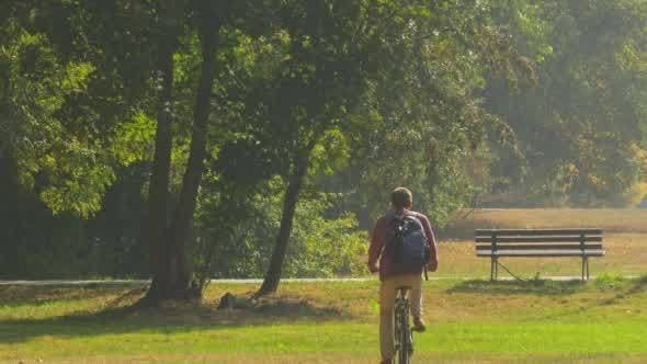 Cover Image for Man by Bicycle Tourist With Backpack is Riding