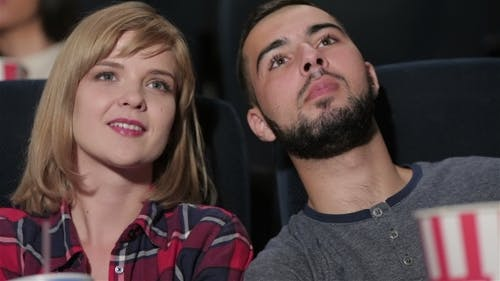 Young Couple Sitting In Multiplex Movie Theater