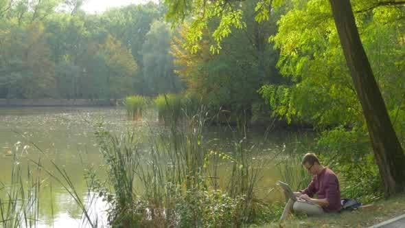 Thumbnail for Man in Glasses is Sitting at the Lake Bank