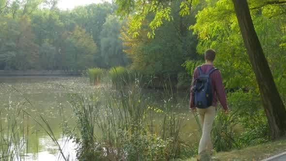 Thumbnail for Man in Glasses With Backpack Comes to Lake Bank