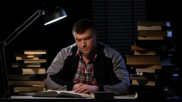 Thumbnail for Man Takes a Book and Writes the Information Itself. Black Background