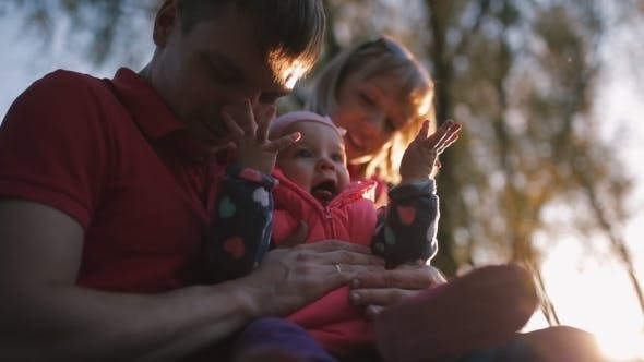 Thumbnail for Happy Family Holding a Baby In Her Arms