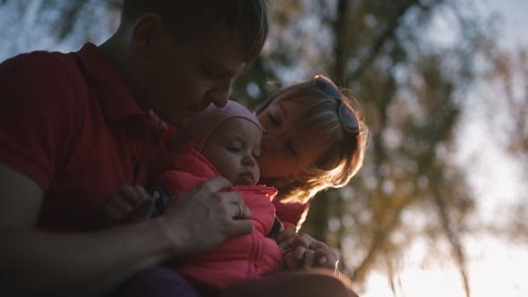 Thumbnail for Happy Family Holding a Child In Her Arms