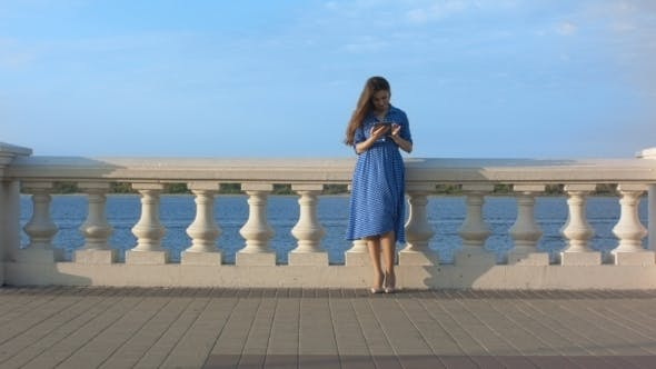 Thumbnail for Beautiful Girl In Blue Dress Using Digital Tablet.