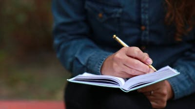 Writer Takes Notes in a Notebook