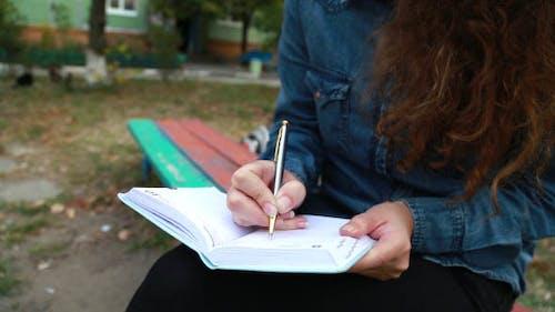 Mädchen im Park schreibt Gedichte