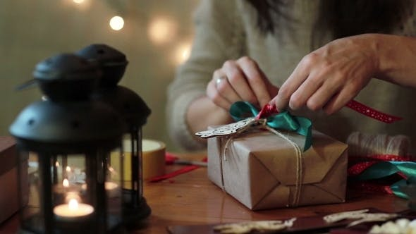 Cover Image for Young Woman Wrapping Christmas Gifts At Home