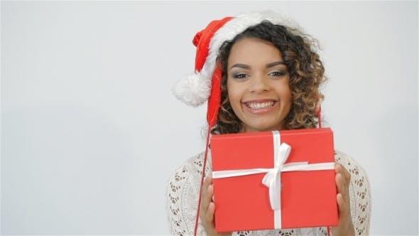 Thumbnail for Fröhlich Mädchen schütteln Weihnachtsgeschenk und lacht
