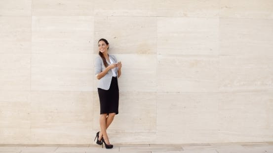 Thumbnail for Stylish Businesswoman Standing Against a Wall