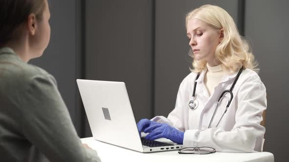 Female Doctor Talking with Patient During Visit at Doctors Office