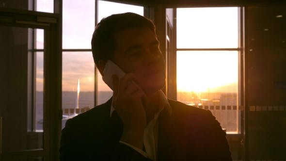 Thumbnail for Man In The Airport Having a Phone Talk At Sunset