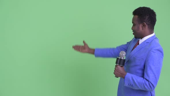 Happy Young African Businessman As Newscaster Presenting Something