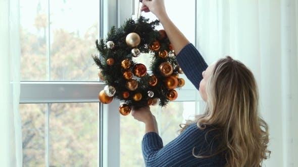 Thumbnail for Girl Hangs a Christmas Wreath On a Window